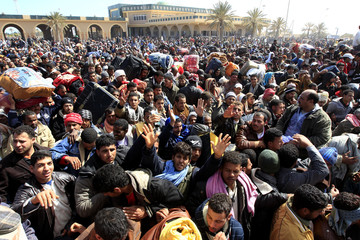 An Egyptian man fleeing the unrest in Libya calls for help as he waits with his compatriots at the Ras Jdir border crossing