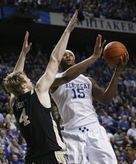 University of Kentucky's Cousins fights to get his shot off under pressure from Vanderbilt University's Ogilvy in Lexington