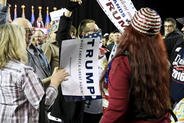 Supporters of U.S. Republican presidential candidate Trump try to block out a protestor at a campaign rally at Oral Roberts University in Tulsa, Oklahoma