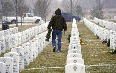 A volunteer looks for the grave of a military veteran to place a Christmas wreath during the Wreaths Across America event at Ft. Logan National Cemetery in Denver