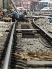 Carpenters work while sitting on the railway track in downtown Hanoi