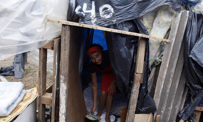 Woman holds her sandal inside her house in a camp erected by an estimated 8,000 members of Brazil's Roofless Workers Movement, who last month occupied a plot in Embu Das Artes