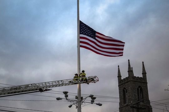 Trinity Episcopal Church is seen in the background as firefighters lower the American flag to half-staff along Main Street in the center of Newtown, Connecticut