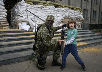 A pro-Russian armed man allows a local boy to hold a machine gun, while standing guard outside the mayor's office in Slaviansk