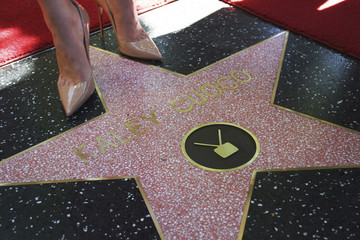 Actress Kaley Cuoco stands on her star at the dedication of her star on the Hollywood Walk of Fame in Los Angeles
