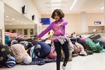A young girl dances with an American flag in baggage claim while women pray behind her at Dallas/Fort Worth International Airport in Dallas