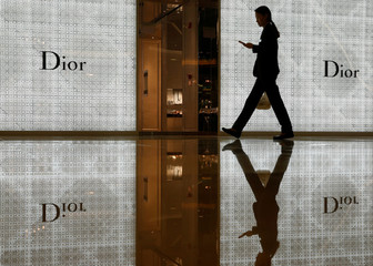 A woman passes a Christian Dior fashion boutique at a mall in Singapore