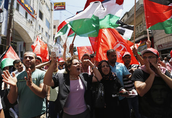 Palestinians wave Palestinian and PFLP flags during protest against renewal stalled peace talks with Israel, in Ramallah