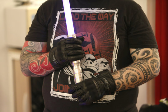 A member of the Sport Saber League with arm tattoos holds his light saber during a training session in Paris