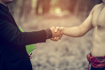 businessman and farmer handshaking for business cooperation and acquisition concept, selective focus and vintage tone
