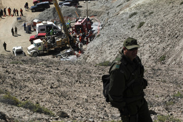 Police officer patrols the area as rescue workers prepare tube for sending supplies at Copiapo
