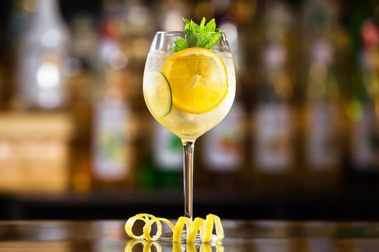 Closeup glass of white sparkling wine sangria decorated with citrus slices at bright bar counter background.