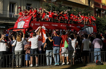Sevilla's team celebrates with their Europa League trophy on an open-top bus in the Andalusian capital of Seville, southern Spain