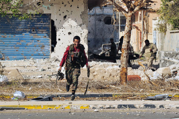 An anti-Gaddafi fighter runs for cover during clashes with Gaddafi forces in Sirte