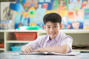 Happy asian child reading book with smile face.