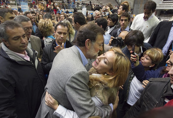 Rajoy, presidential candidate of Spain's centre-right People's Party embraces a supporter after an electoral rally outside Madrid