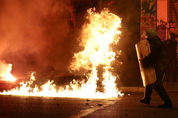 Policemen run between exploding petrol bombs following a rally marking the 43nd anniversary of a 1973 student uprising against the military dictatorship