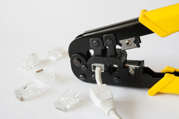 Crimping tool for twisted pair network cable with connectors on white background. Crimping pliers closeup.