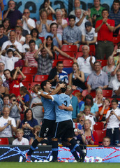 Team mates hug goalscorer Nicolas Lodeiro during their football match against the UAE at the London 2012 Olympic Games in Old Trafford