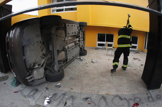 A firefighter picks up an axe next to an overturned car, during a fire in the state building of the Party of the Democratic Revolution in Chilpancingo, Guerrero