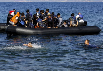 An Afghan refugee tries to swim towards the shore after jumping into the water without a life vest from a dinghy with a broken engine overcrowded with Afghan refugees, which drifted out of control off the Greek island of Lesbos