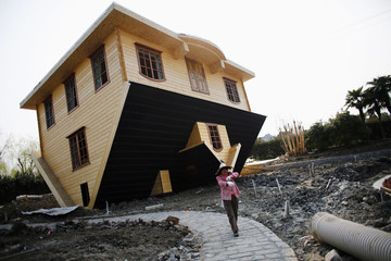 A labourer works at an upside-down house under construction at Fengjing Ancient Town, Jinshan District