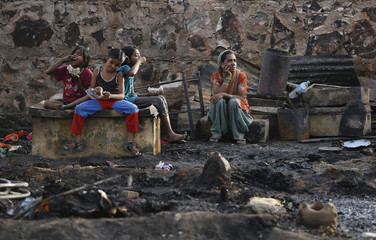 A family sits amid the burnt debris of their hut after a fire broke out in a slum area in New Delhi