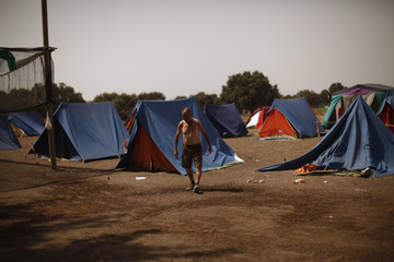 Member of SAT walks past tents on hot day summer at the Turquillas land in Osuna