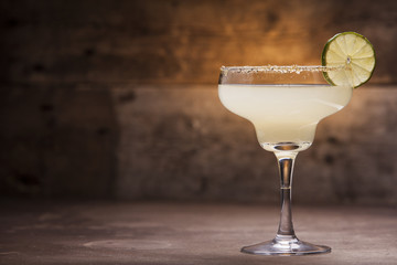 Classic Margarita cocktail on wooden background