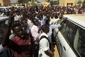 Students shout as they surround United Nations-African Union Mission in Darfur vehicles in Zalingi town in west Darfur