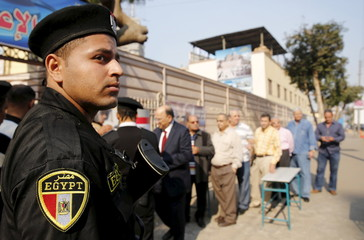A policeman stands guard in front of people lining up to vote, outside a school being used as a polling station during the second round of parliament elections at Heliopolis in Cairo, Egypt
