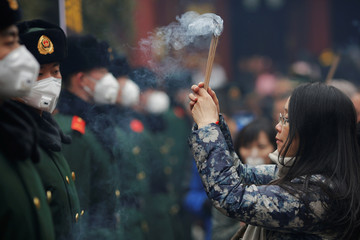 A woman holds incense sticks in front of paramilitary policemen providing security as people gather at Yonghegong Lama Temple to pray for good fortune on the first day of the Lunar New Year of the Rooster in Beijing