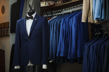 Elegant male mannequin presenting luxury suits tuxedo and male fashion accesories
