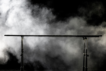 Closeup. Gymnastic parallel bars. Isolated on black background with fog,