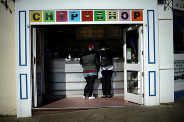 Youths wait for fish and chips at a local chip shop in Scarborough