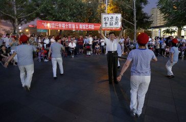 Local resident holds paper card as women perform anti-Japanese dance in Beijing