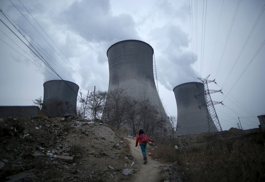 A girl makes her way to her house which locates next to cooling towers of coal-fired power plant in Shijiazhuang