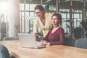 Two young businesswomen working.Teamwork.Girls blogging,working,learning online.Online education,marketing. Instagram filter.