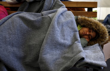 A migrant sleeps as she wait to get on a train to Serbia at a transit camp on the Macedonia-Greece border near Gevgelija