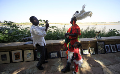 An artist takes photographs of the a traditional dancer during an open air exhibition along the bank of the Blue Nile in Khartoum