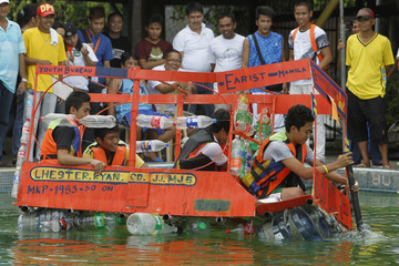 Students test the stability of an improvised raft made out of recycled material during a boat-making competition in Manila