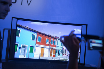 Person takes photo of the Curved OLED TV during a news conference in New York