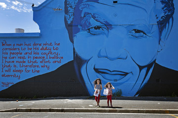 India Harris, age eight, and her sister Kitty, five, stand in front of a Nelson Mandela wall mural shortly after laying bouquets of flowers for the late former South African president in Cape Town