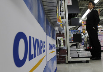 A man stands near Olympus' logos at an electronics shop in Tokyo
