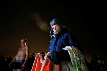 A young man holds towels during Orthodox Epiphany celebrations in Yaroslavl, Russia