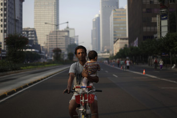 A father holds his child while riding a bicycle during Car Free Day at the main street in Jakarta