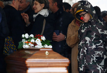 A kid wearing a clown nose, looks at the coffin of Italian Nobel-winning playwright and master satirist Dario Fo during his funeral in Duomo square in Milan