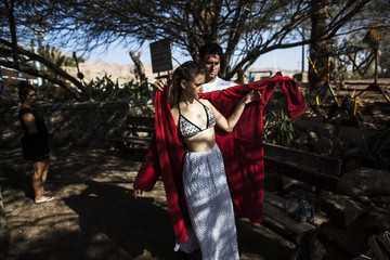 A stylist helps a model put on a robe before an underwater photo shoot in the Red Sea in Eilat