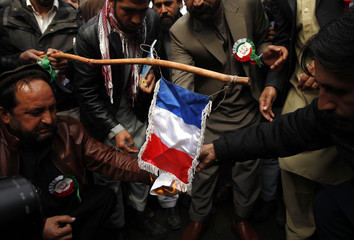 Afghans set fire to a French national flag during a demonstration against the satirical French weekly Charlie Hebdo's cartoons of the Prophet Mohammad, in Jalalabad city