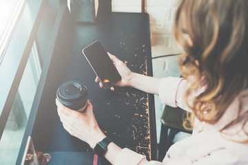 Top view. Close-up of smartphone and cup of coffee in hands of hipster girl sitting in cafe at black table.